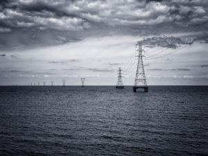 Power line towers receding across a lake