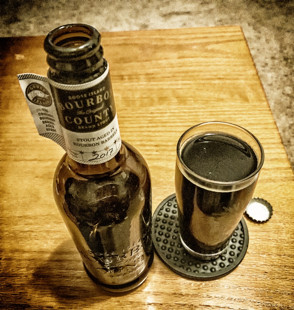 A high-angle, heavily edited photo of a bottle of Goose Island Bourbon County Barrel Stout from 2017, next to a small glass filled with it.