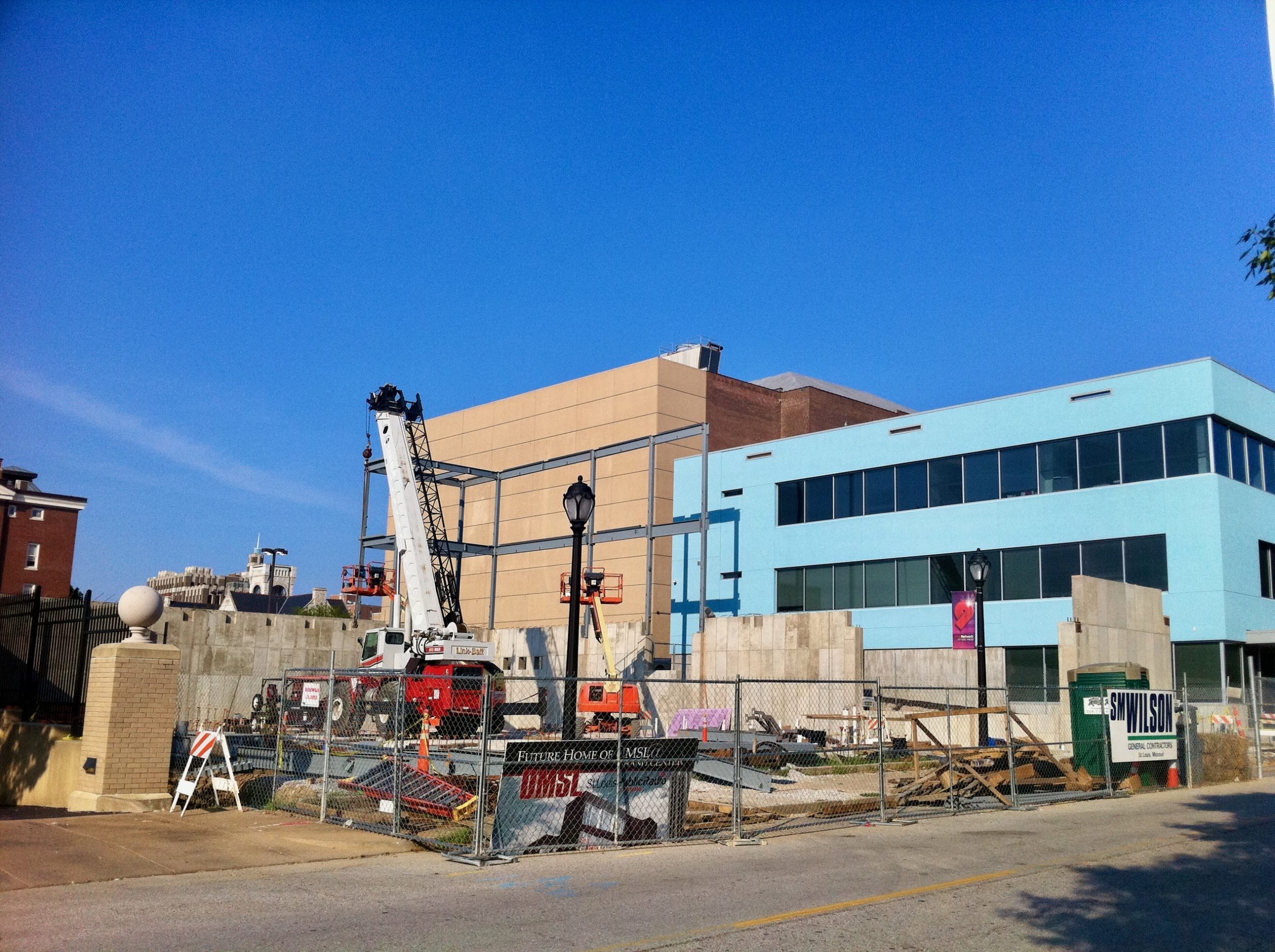 An image of a construction site, the future home of St. Louis Public Radio. There are some concrete walls and the start of a steel skeleton.