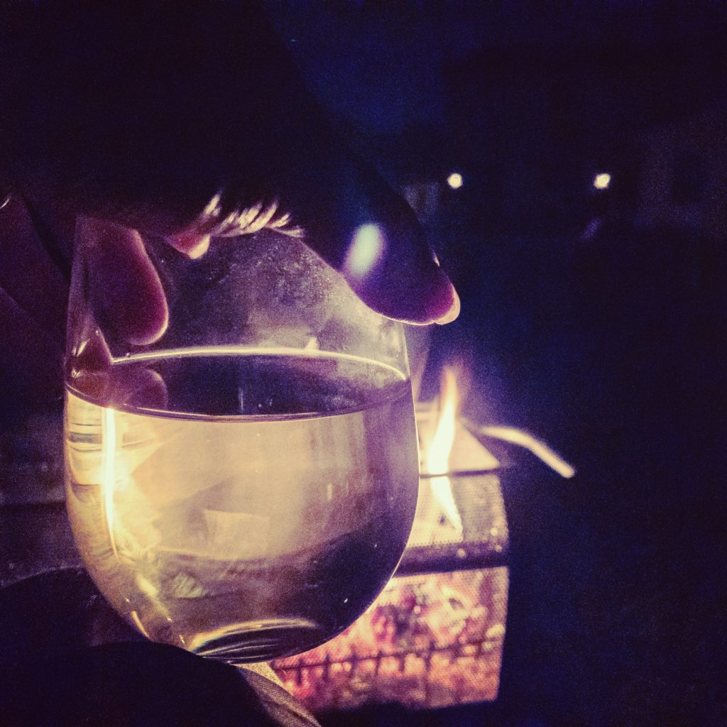 A hand holding a glass of wine in front of a small bonfire.