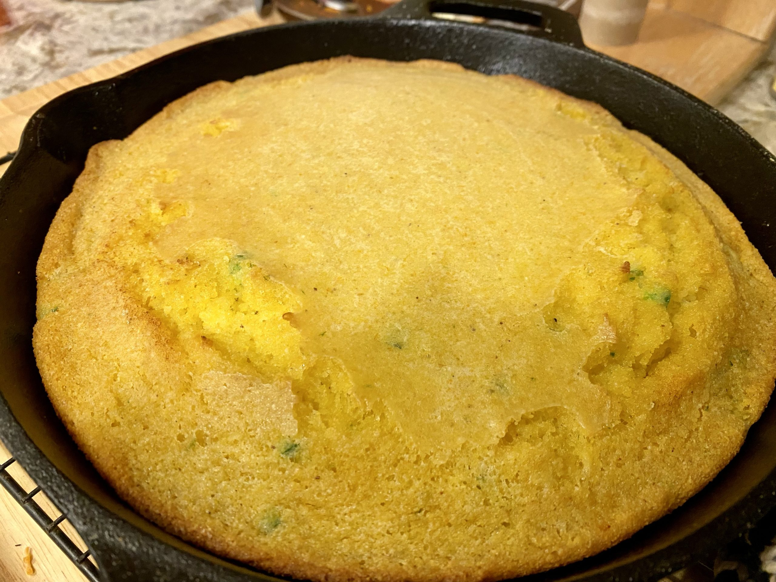 A photo of cooked cornbread in a cast iron skillet